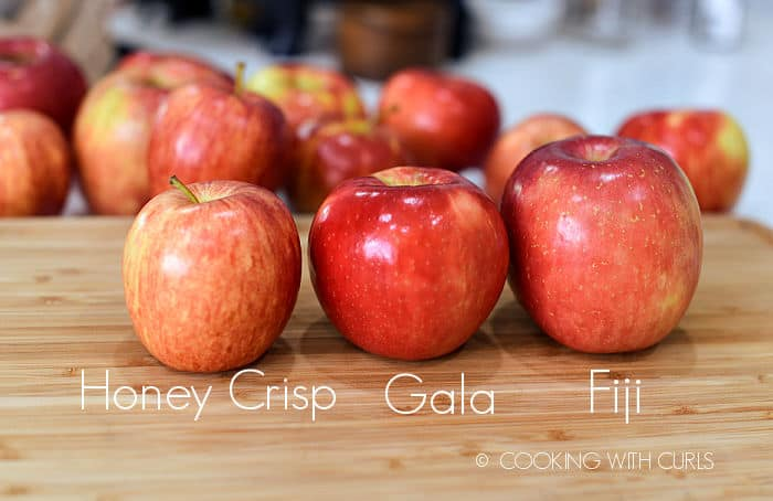 a honey crisp, gala, and fuji apple lined up on a wood cutting board with more apples in the background.