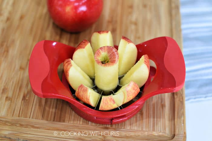 an apple cut into wedges on a wood cutting board with a red, plastic wedge cutter and a whole apple in the background.