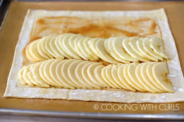 apple slices laid on top of puff pastry in two rows with remaining apple butter showing through.