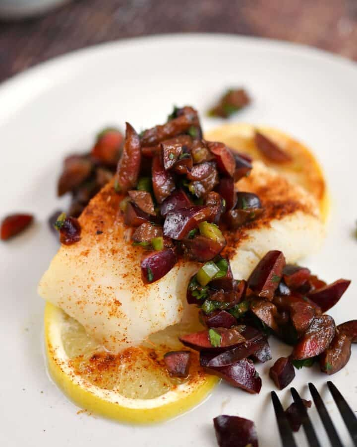 baked cod topped with cherry salsa sitting on two lemon slices on a white plate.