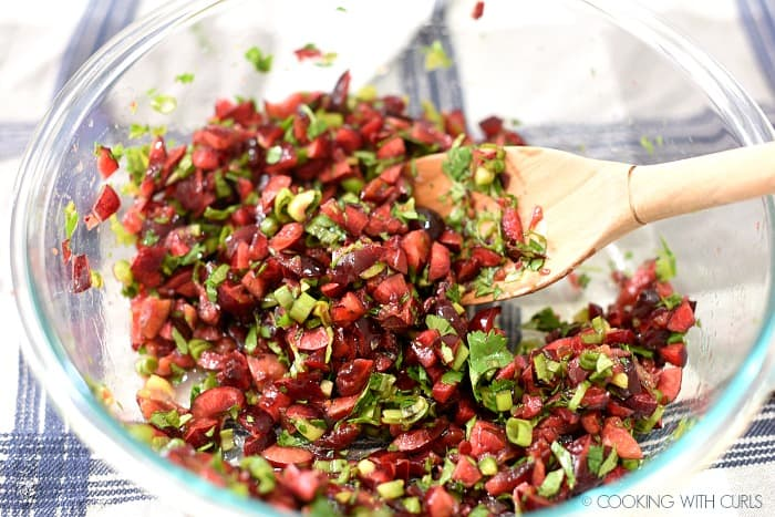 chopped cherries, jalapeno, green onions and cilantro mixed together in a clear glass bowl.