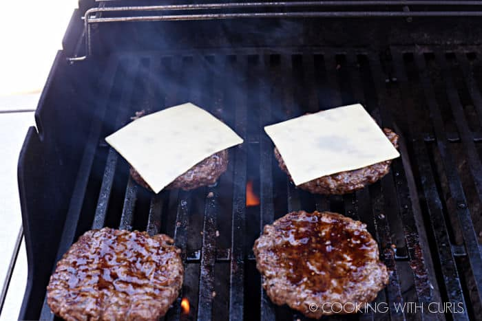 four cooked beef patties brushed with teriyaki sauce, two with a slice of white cheddar cheese on top cooking on a barbecue grill.