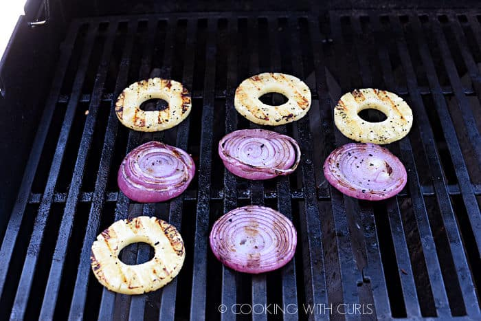 four grilled pineapple and red onion slices on the grill with grill marks on one side.