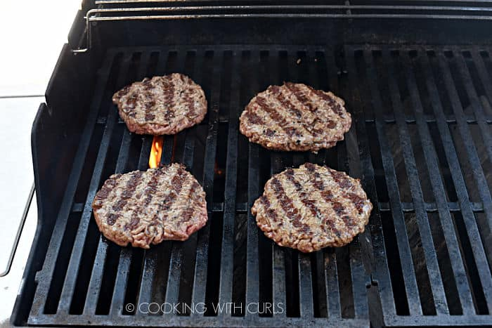 four ground beef patties with grill marks on one side cooking on a gas barbecue grill.