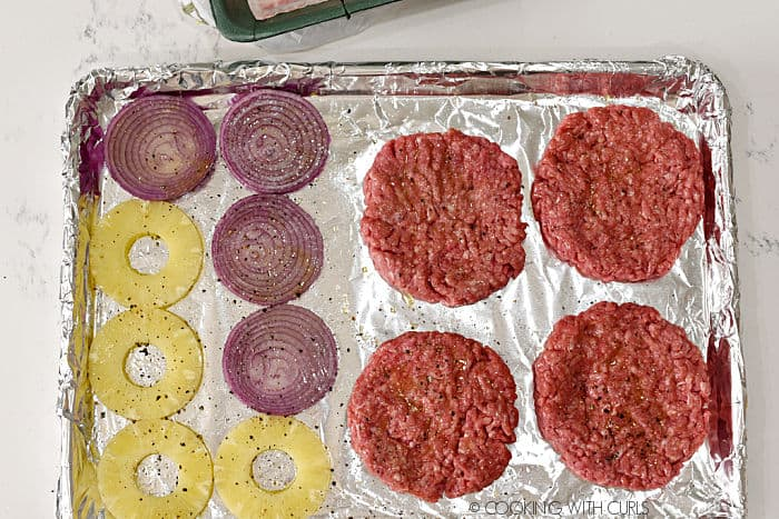 four pineapple rings, four red onions slices and four ground beef patties flattened out on a foil lined baking sheet.