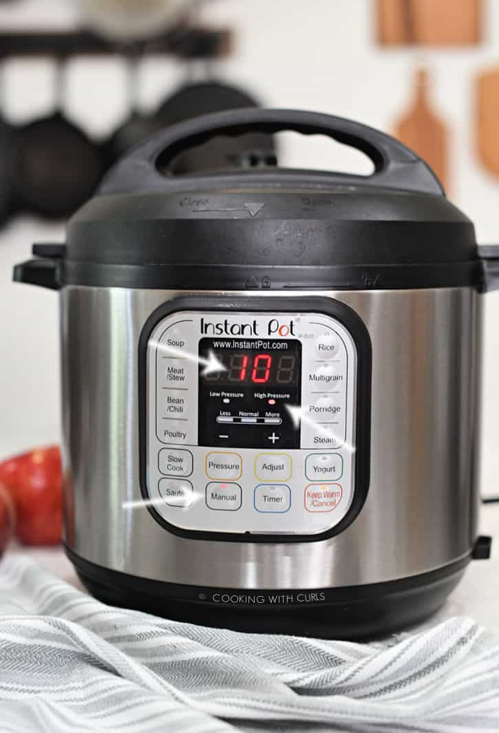 instant pot set for 10 minutes on manual high pressure with arrows pointing to each illuminated button.