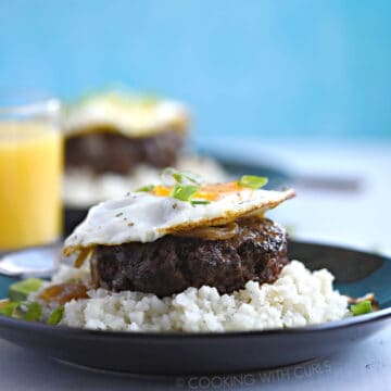 A ground hamburger steak patty topped with rich gravy and fried egg sits atop steamed rice and is garnished with green onions with a glass of orange juice and a second plate of food in the background.