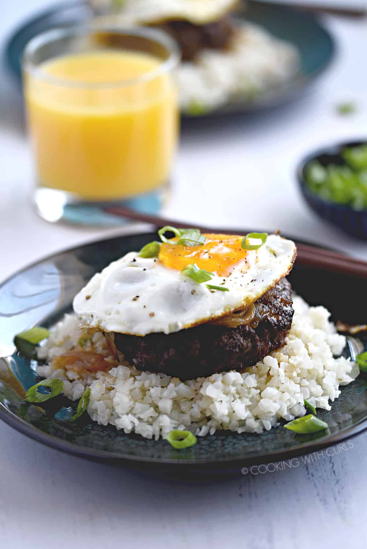 a burger patty topped with brown gravy, fried egg and green onions on a bed of rice with a glass of orange juice and a second plate of food in the background.