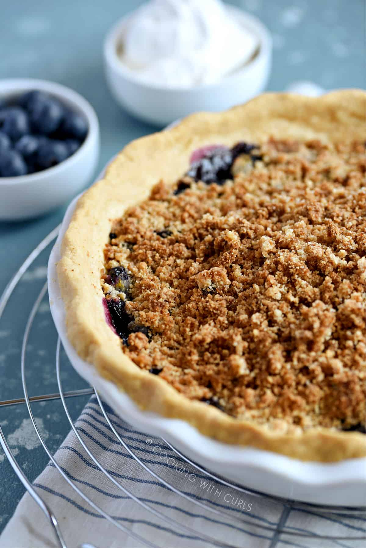 a close-up picture of a hot, fresh blueberry crumb pie on a wire cooling rack sitting on a blue and white towel with a bowl of blueberries and a bowl of whipped cream in the background.