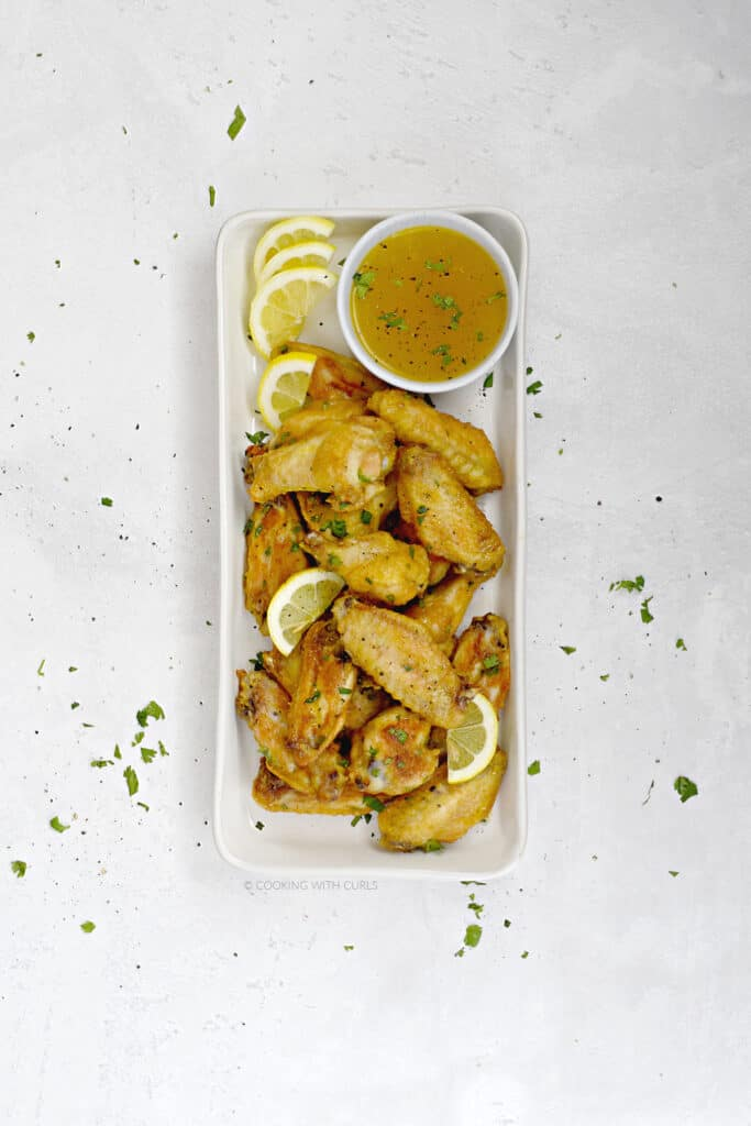 Looking down on crispy Baked Lemon Garlic Chicken Wings with extra dipping sauce on a white, rectangle platter.