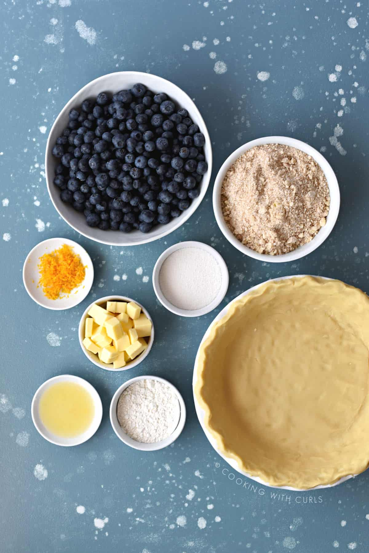 a large white bowl filled with fresh blueberries, a bowl with crumb topping, small bowls with orange zest, sugar, flour, orange juice and a pie crust in a white pie pan.