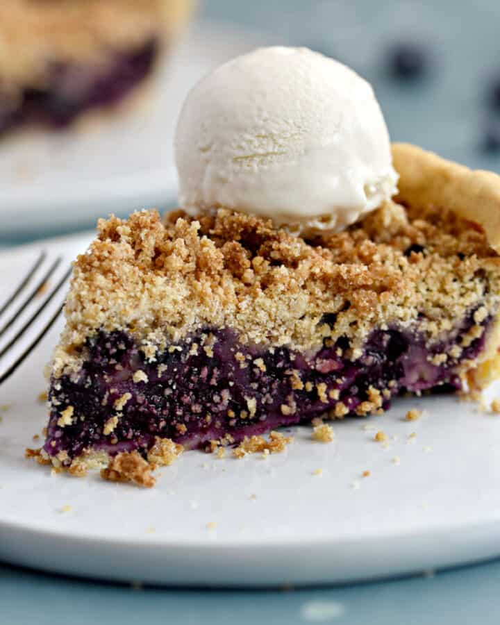 a slice of fresh blueberry crumb pie topped with ice cream on a white plate with a second pie in the background.