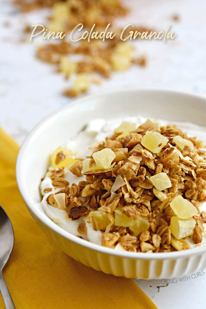 Pina Colada Granola topped yogurt in a white ribbed bowl sitting on a yellow napkin with a spoon to the left and spilled granola at the top.
