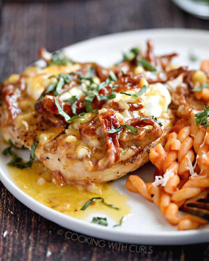 a close-up image of Chicken Bryan with a side of pasta on a white plate.