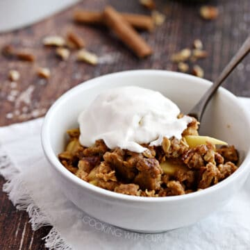 a white bowl with apple crisp topped with vanilla ice cream sitting on a white fringed napkin with an apple and baking dish in the background.