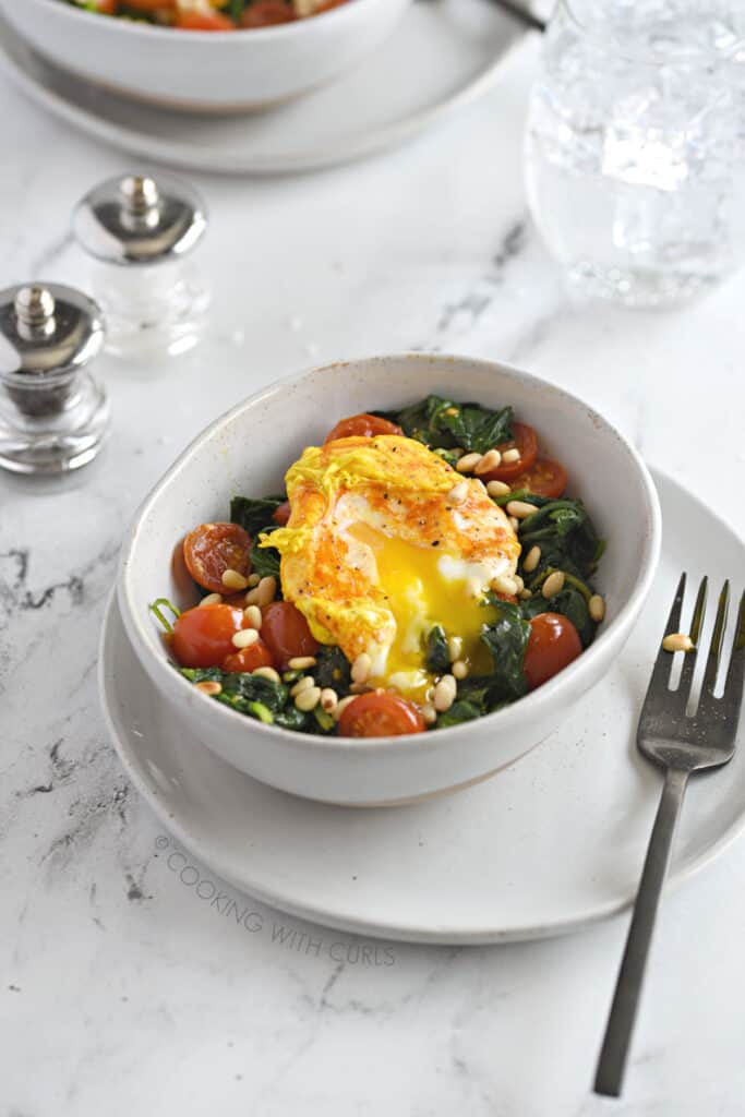 a turmeric poached egg in a white bowl, broken open over sauteed spinach and tomatoes and sprinkled with toasted pine nuts.