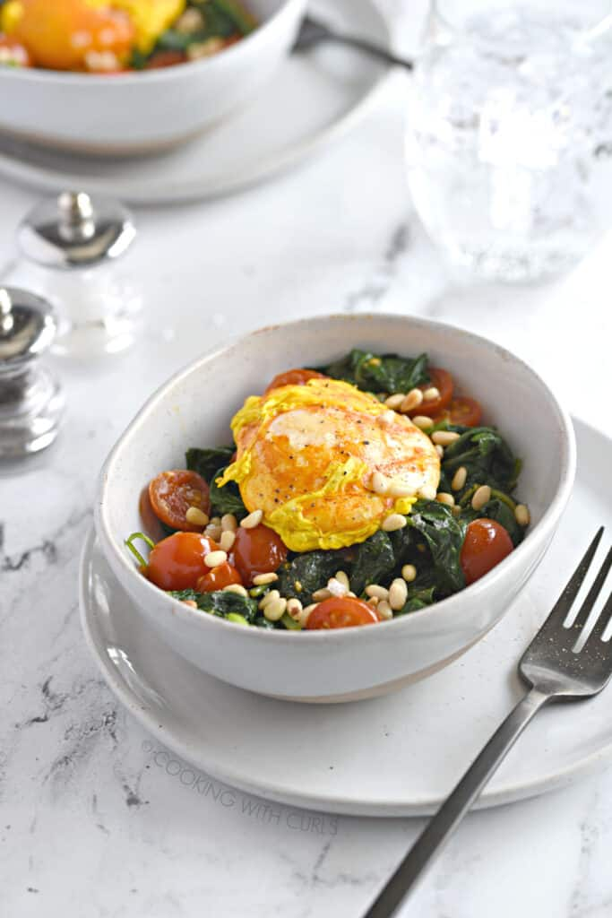a turmeric poached egg in a white bowl sitting on a bed of sauteed spinach and cherry tomato halves sprinkled with toasted pine nuts.