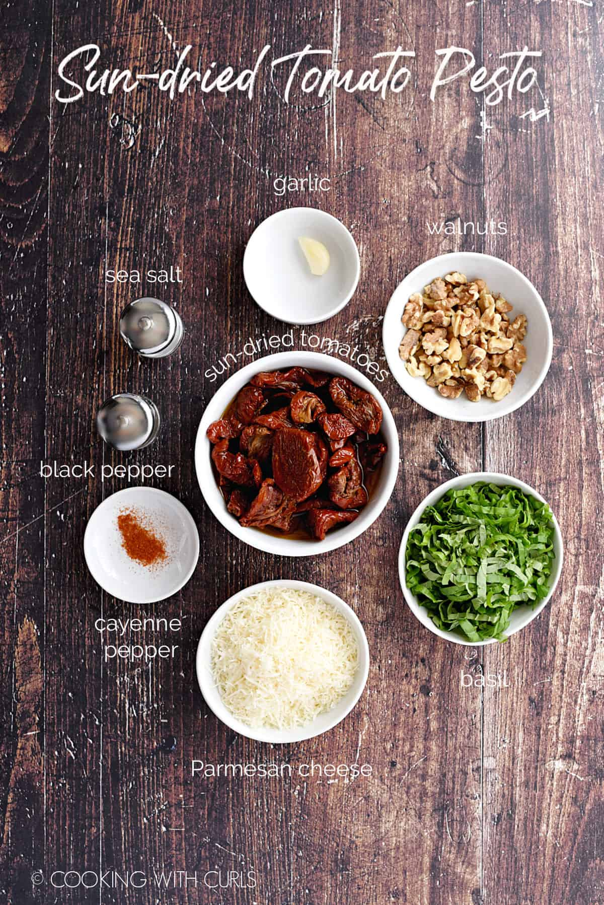Sun-dried Tomato Pesto ingredients in small white bowls; garlic, walnuts, basil, parmesan cheese, sun-dried tomatoes, cayenne, salt, pepper.