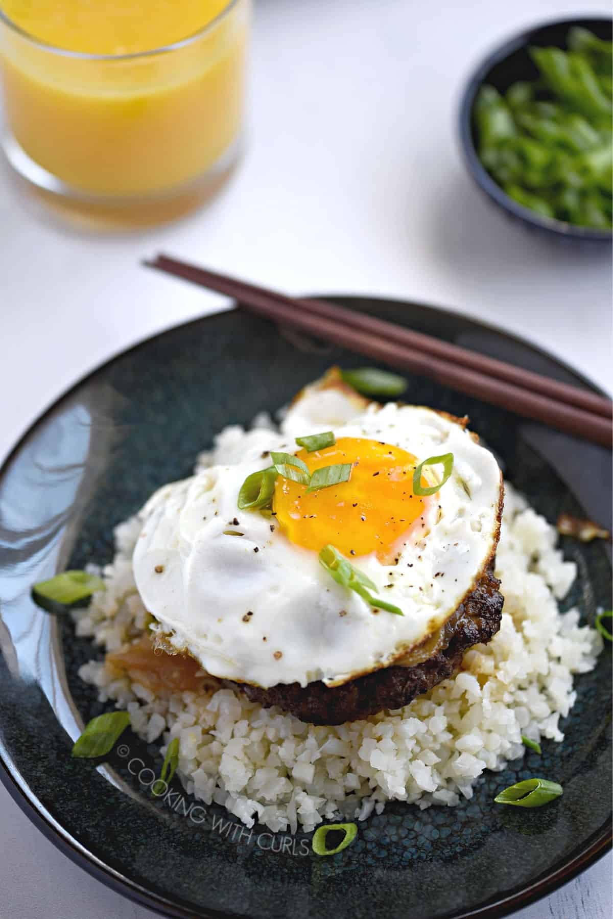 looking down on a sunny-side up egg on top of a burger patty covered in gravy on a bed of rice with a glass of orange juice and small bowl of green onions in the background.