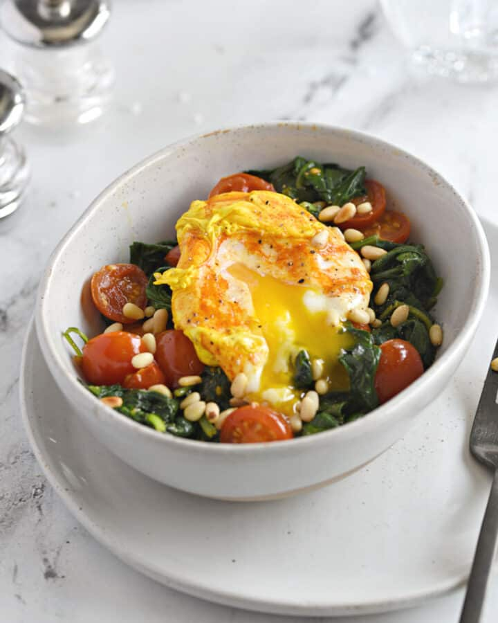 a turmeric poached egg split open over a bed of sauteed spinach and cherry tomato halves sprinkled with toasted pine nuts.
