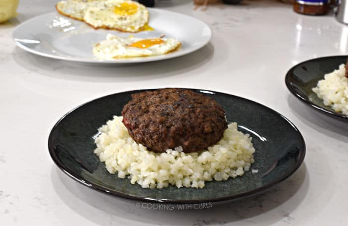 a cooked burger patty on a bed of rice with a plate of fried eggs in the background.