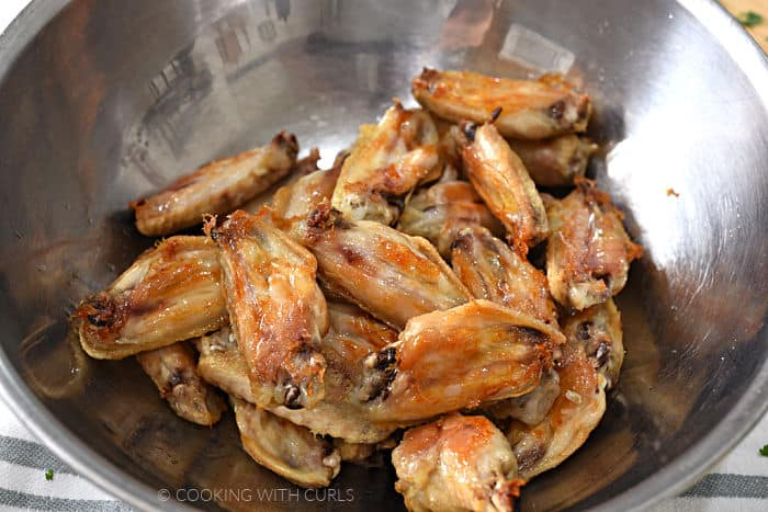 a stainless steel bowl filled with baked chicken wings.