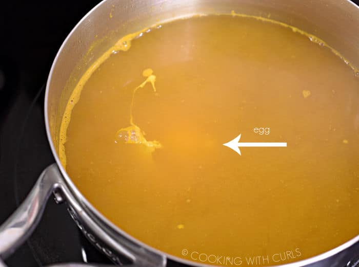 an egg dropped into the hot turmeric water in the saucepan.