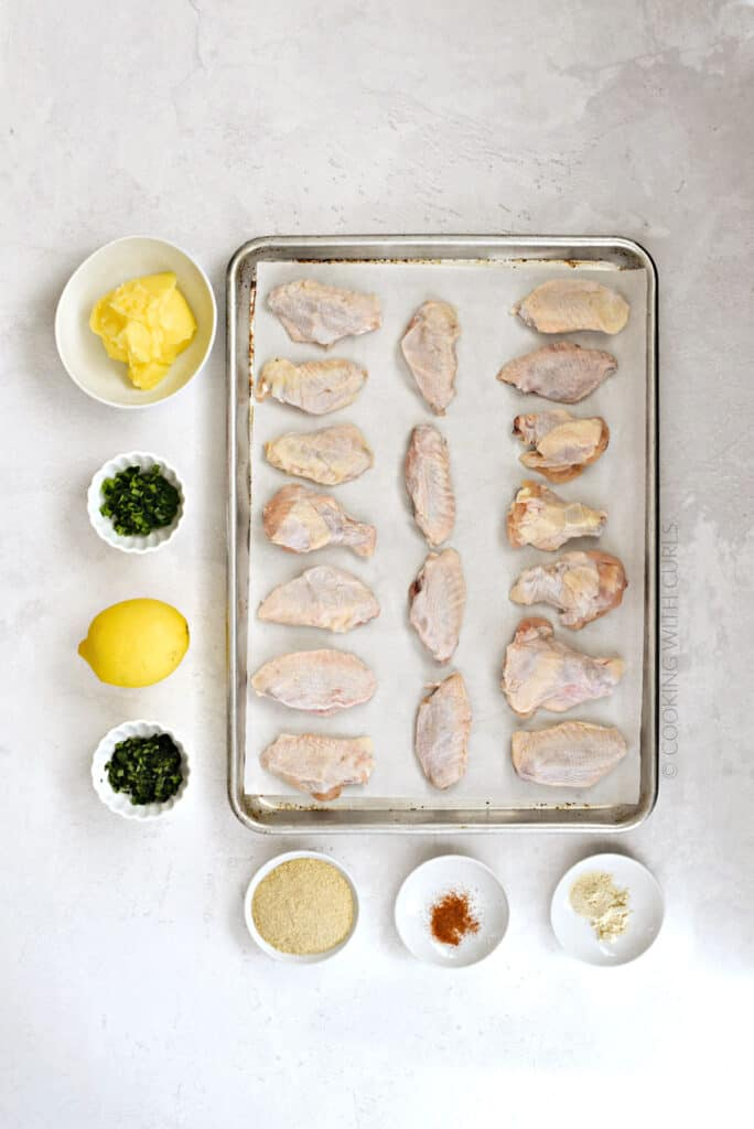 chicken wings on a parchment lined baking sheet with butter, garlic and herbs in white bowls around the pan.