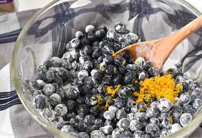fresh blueberries tossed with sugar, orange zest and orange juice with a wooden spoon in a large glass bowl.
