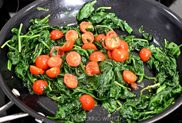 spinach, garlic and tomatoes cooked down in a large non-stick skillet.