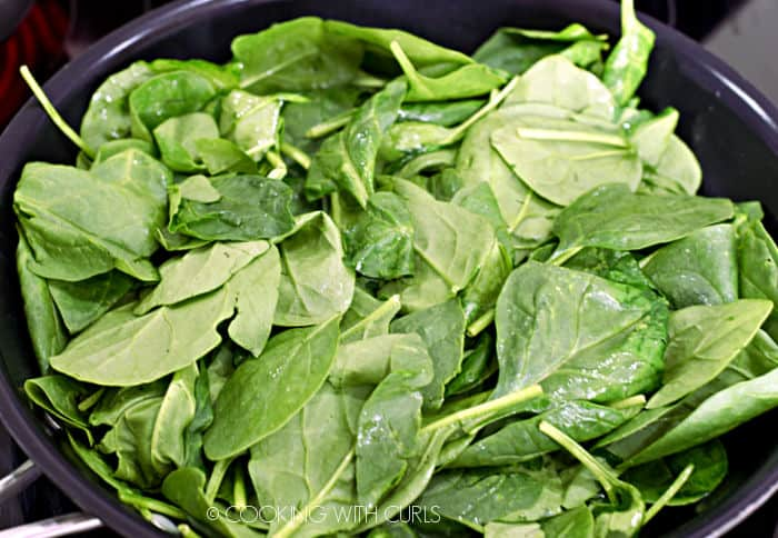 spinach tossed in oil in a large non-stick skillet.
