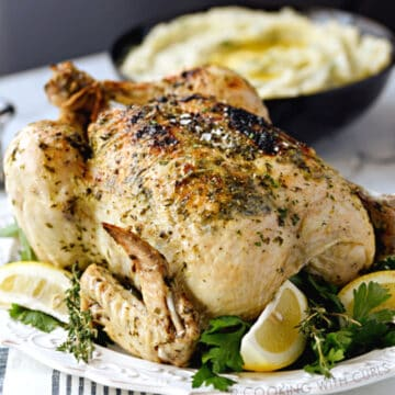 An Instant Pot Whole Greek Chicken on a white platter with thyme and lemon wedges, with a bowl of mashed potatoes in the background.