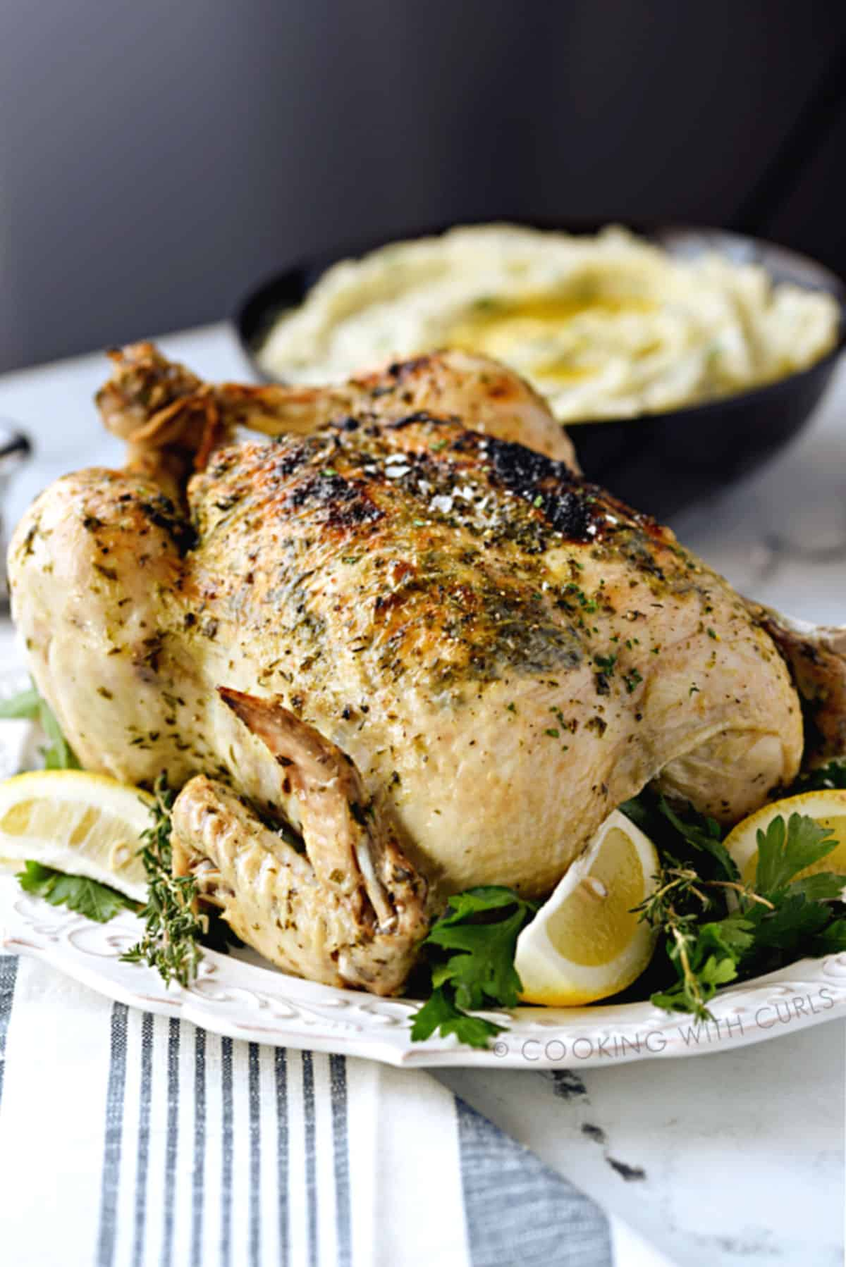 A whole Greek chicken on a white platter surrounded by fresh herbs and lemon wedges with a bowl of mashed potatoes in the background.