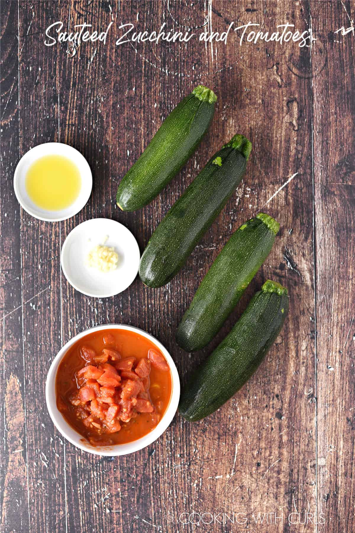 Ingredients to make Sauteed Zucchini and Tomatoes with four medium zucchinis, a bowl of diced Italian tomatoes, minced garlic and olive oil in small white bowls.