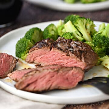 sliced filet mignon on a white plate with broccoli florets, with a second plate in the background.