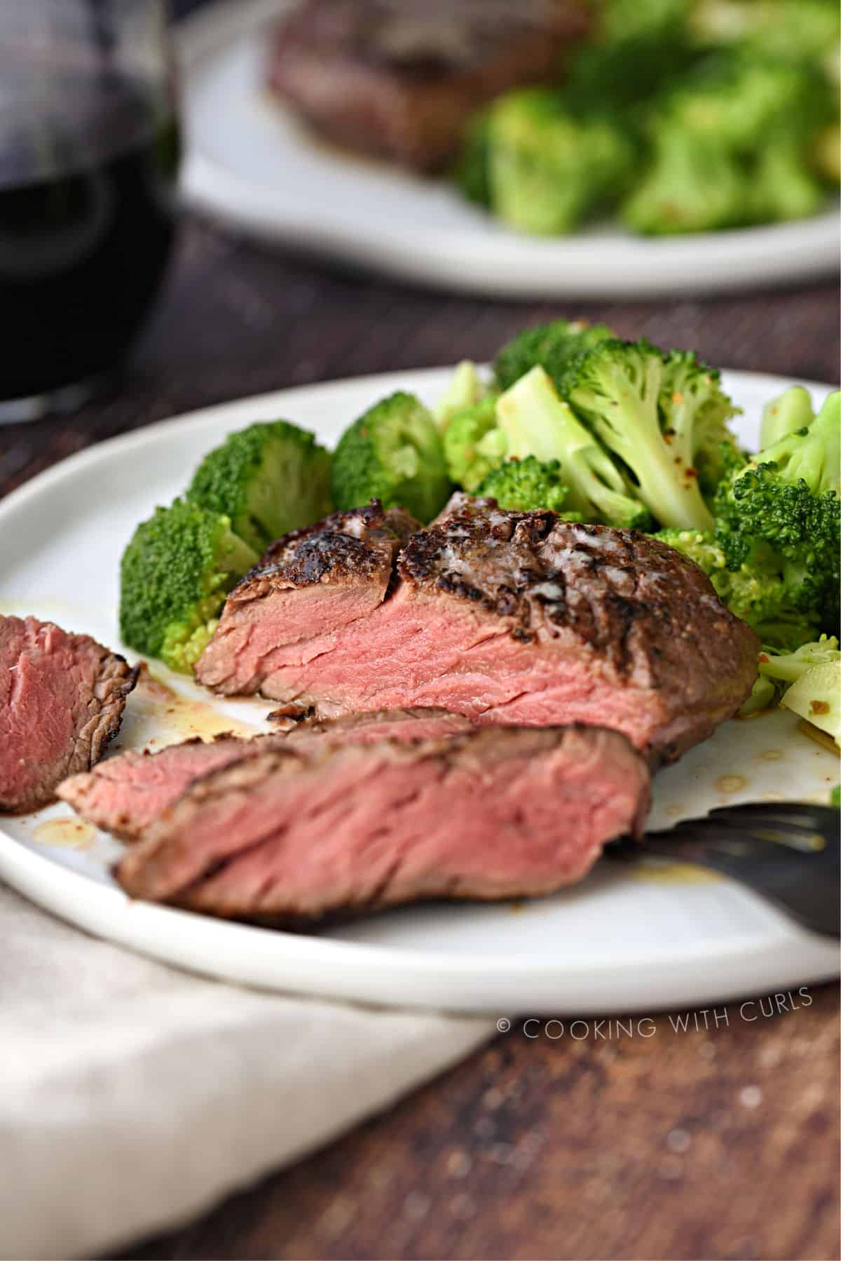 sliced filet mignon on a white plate with broccoli florets, with a second place and a glass of red wine in the background.