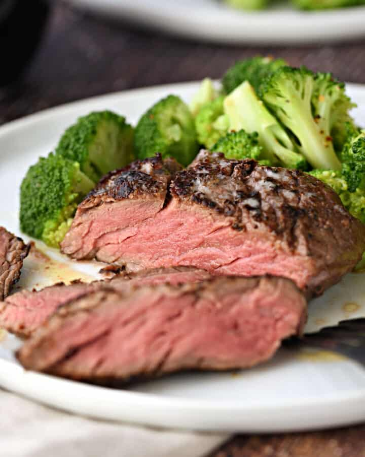 Perfectly cooked Sous Vide Filet Mignon in an Instant Pot sliced on a white plate with broccoli florets on the backside.