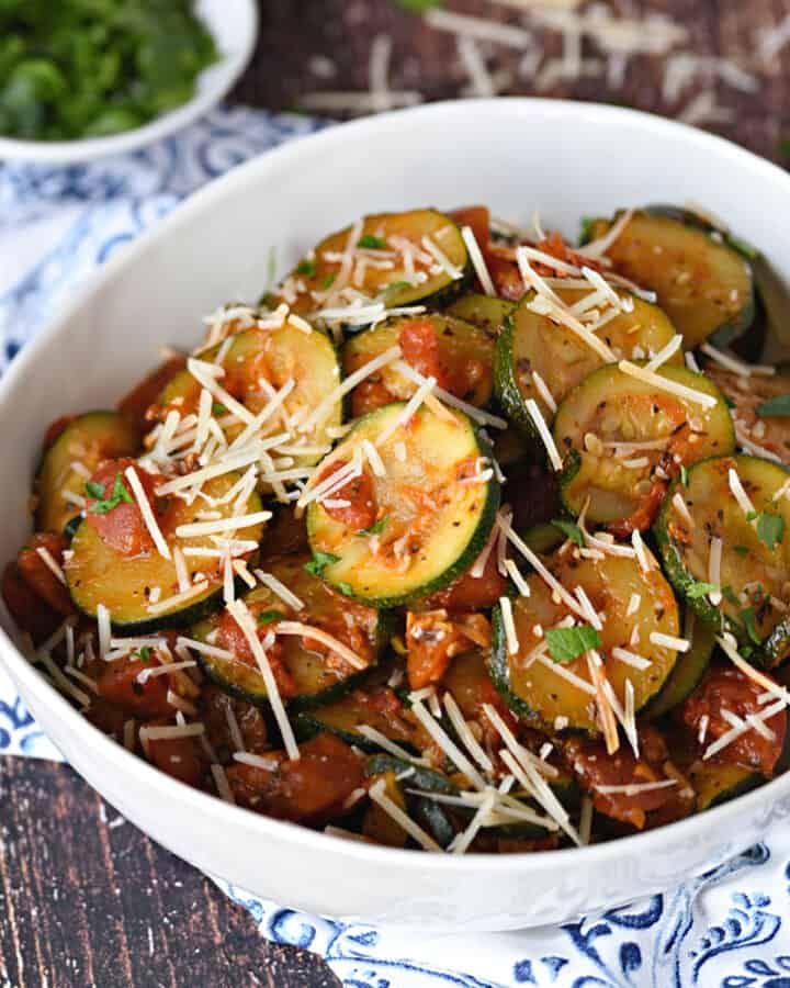 a large white bowl filled with Sauteed zucchini slices and diced tomatoes topped with grated Parmesan cheese and chopped parsley.