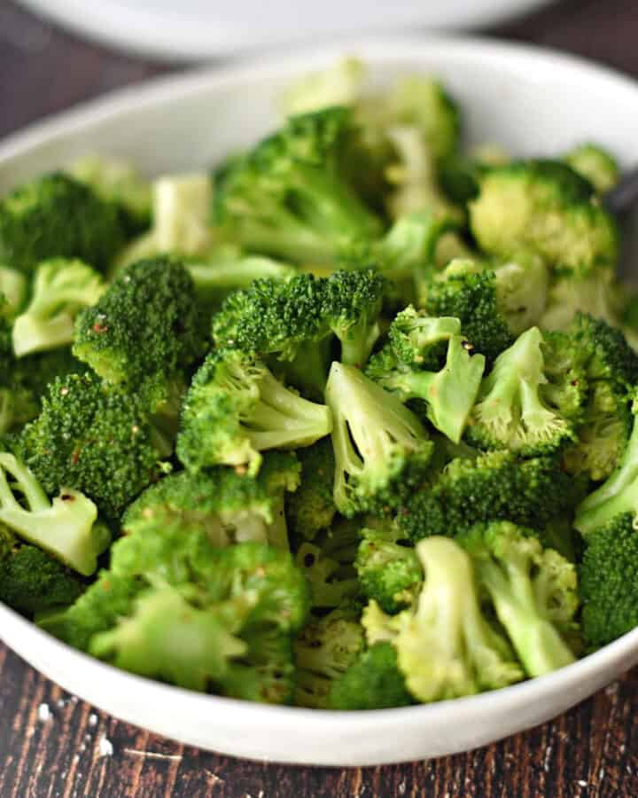 steamed broccoli in a large white bowl.