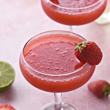 two frozen strawberry daiquiri in coupe glasses with a strawberry garnish.
