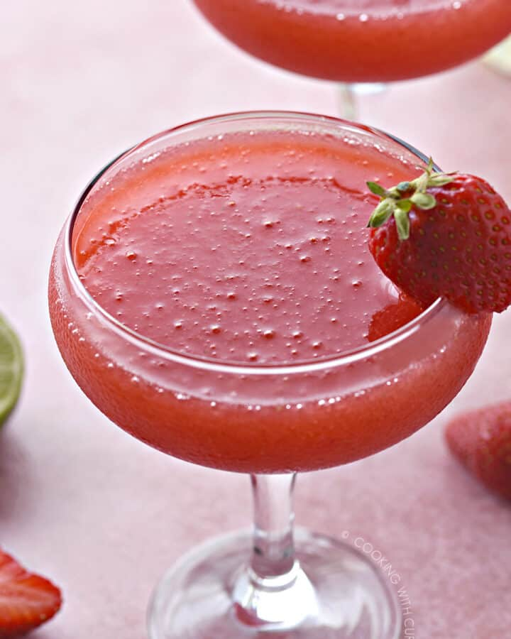 a close up image of a frozen strawberry daiquiri in a coupe glass with a whole strawberry stuck onto the rim of the glass.