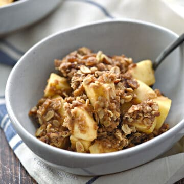 Instant Pot Apple Crisp in a white bowl with a black spoon leaning against the edge.
