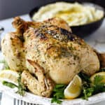 An Instant Pot Whole Greek Chicken on a white platter with thyme and lemon wedges, with a bowl of mashed potatoes in the background and title across the top.