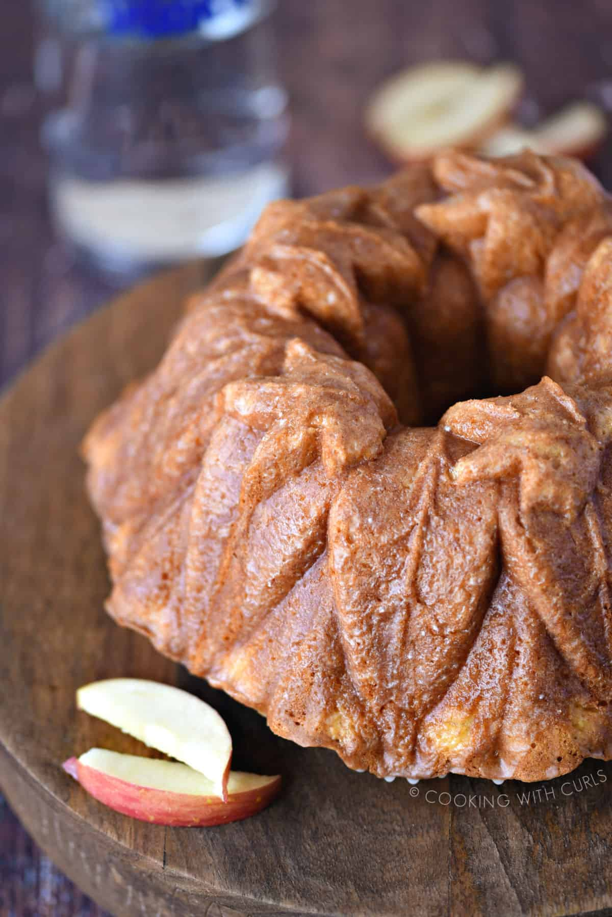 a close up view of a cake baked in a fall leaves bundt pan sitting on a wooden cake plate with two apple slices sitting on the side.