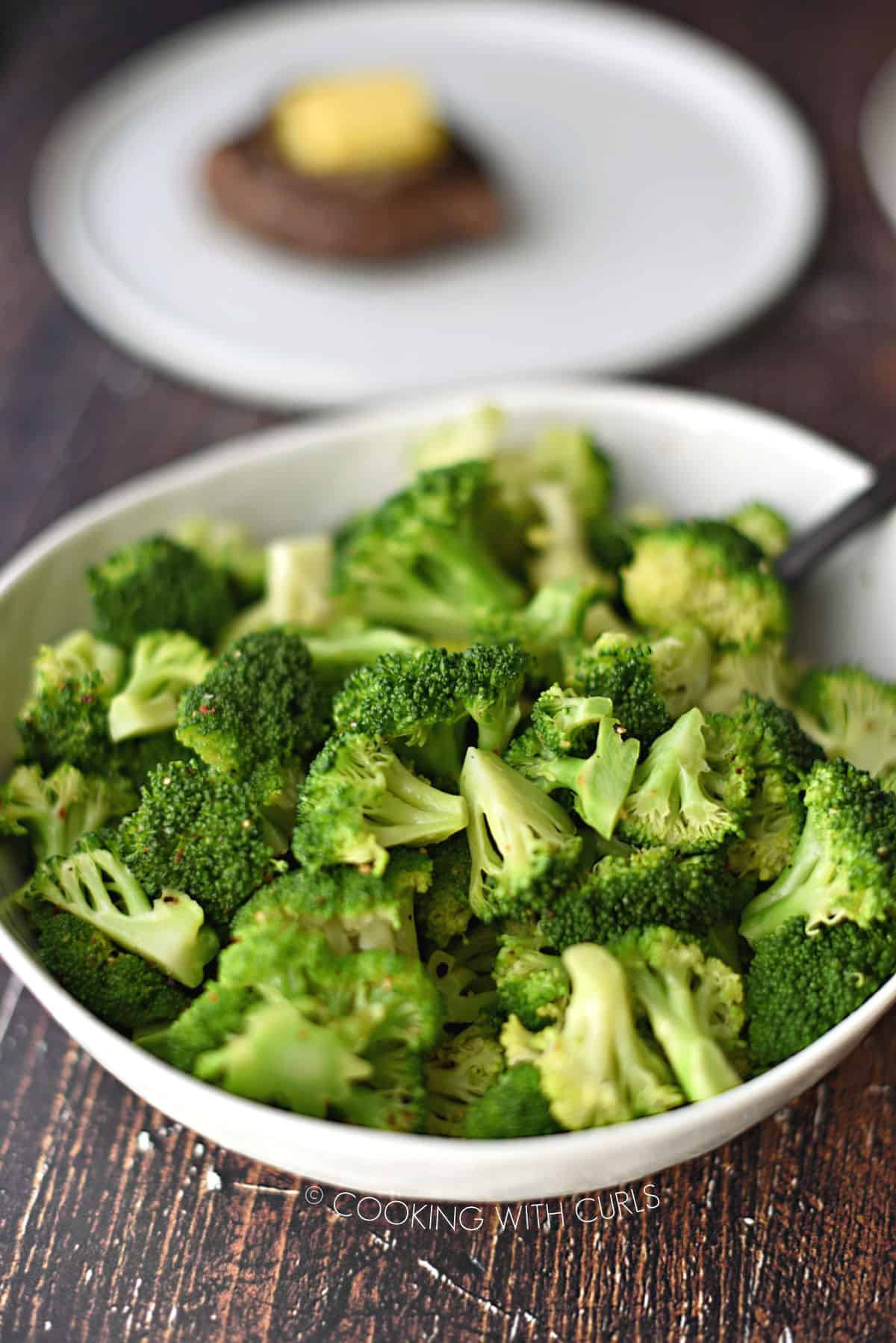 a large white bowl filled with steamed fresh broccoli florets with a white plate topped with a steak in the background.