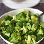 steamed broccoli in a large white bowl tossed with butter and garlic pepper seasoning with title graphic across the top.