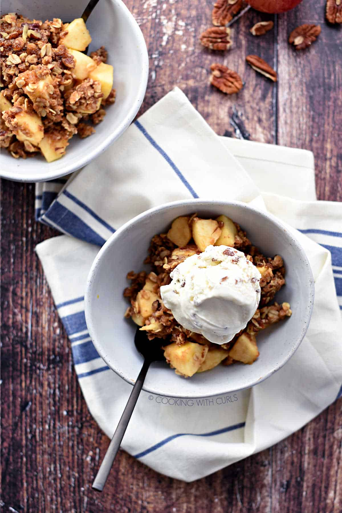 looking down on two white bowls with apple crisp. One is topped with a scoop of ice cream and a black spoon, sitting on a beige and blue striped napkin, the other is plain.