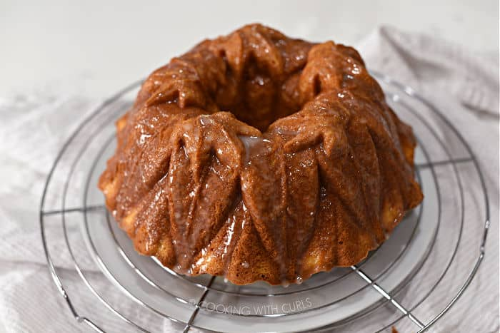 baked bundt cake with glaze poured over the top sitting on a wire rack that is sitting on a large white plate.