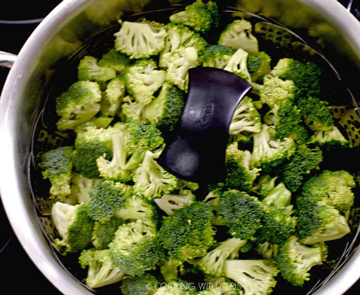 looking down on a metal steamer basket filled with fresh broccoli florets in a large pot.