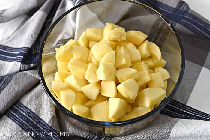 peeled, chopped apples in a glass bowl sitting on a blue, gray and white striped dish towel.